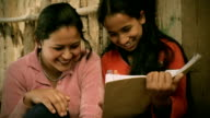 Asian people: Teenage girl showing book to her elder sister video
