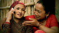Asian people: Two mature, Nepalese women talking on phone happily. video