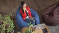 Asian professional woman talking on the smartphone sitting in color chair upper view video