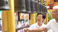 Asian senior couple doing ritual bell ringing in Buddhist temple believe for good luck video