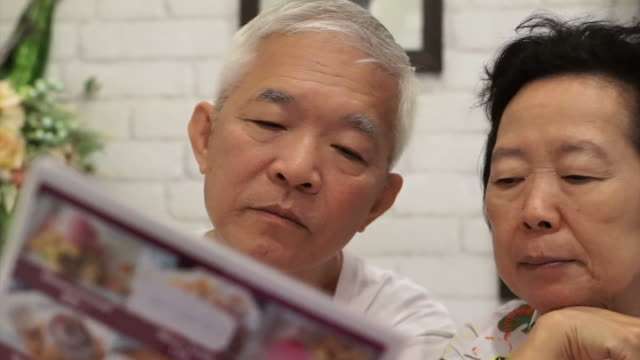 Asian senior couple looking at menus in a restaurant together video