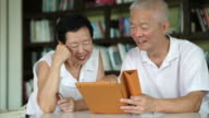 Asian senior couple reading news together from tablet in small library. Learning and study concept video
