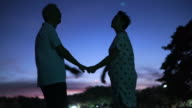 Asian senior couple silhouette with early morning sky and moon background. Secure and happy life abstract video