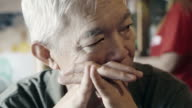 Asian senior guy with hand on face and thinking video