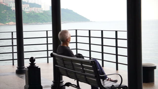 Asian senior man standing alone at the beach front pier in gloomy rainy day video