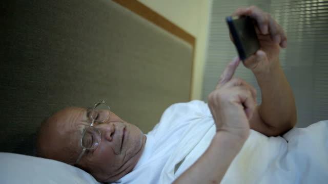 Asian senior man using moble phone indoors video