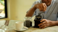 Asian senior man with vintage coffee grinder video