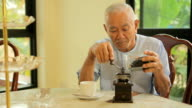 Asian senior man with vintage coffee grinder video