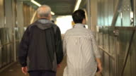 Asian senior retired couple walking holding hands along the cover walkway from train station to condominium video