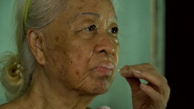 Asian senior woman minerals pills in hand and taking glass of water. video