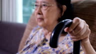 Asian senior woman sitting in chair holding walking stick video