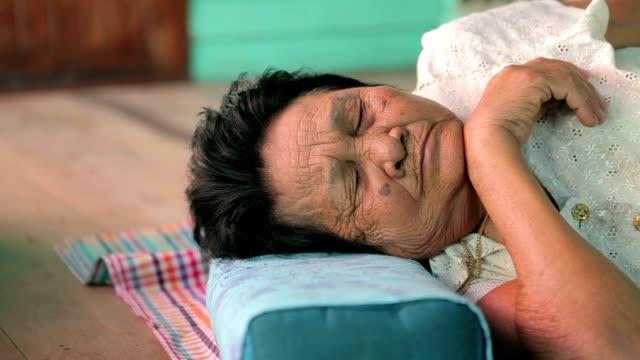 Asian senior woman sleeping on wood video