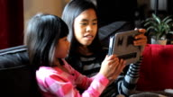 Asian Sisters Playing Games On Tablet Together video