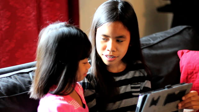 Asian Sisters Watch Movie On Tablet Together video