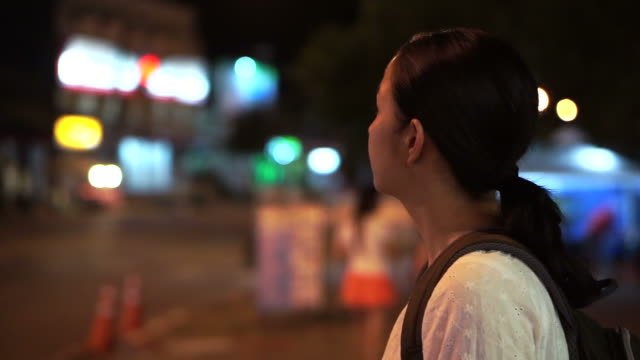 Asian tourist girl wandering in the city at night looking confuse thinking and lost video