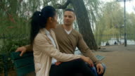 HD: Asian Woman and Biracial Man Talking on a Bench video