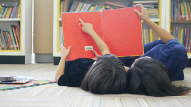 Asian woman and girl reading book in library video
