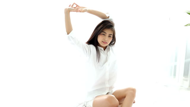 Asian woman Beautiful young smiling woman sitting on bed and stretching in the morning at bedroom after waking up in her bed fully rested video
