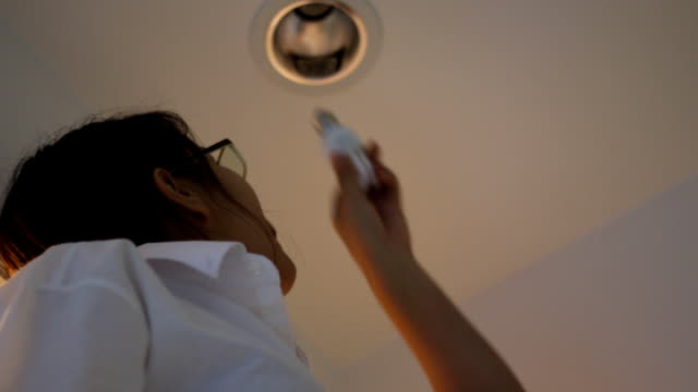 Asian woman changing the bulb in her room, video