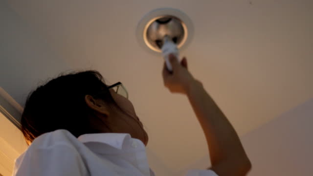 Asian woman changing the bulb in her room,Do it by herself video