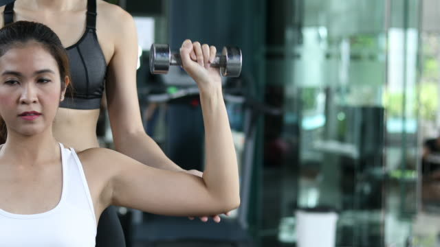 asian woman does dumbell curl exercises in gym video