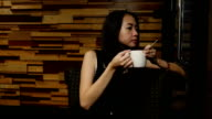 Asian woman drinking coffee in a cafe video