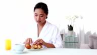 Asian woman having breakfast in bathrobe video