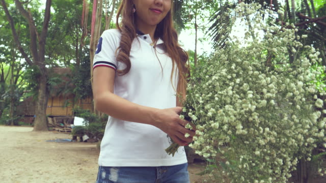 Asian Woman Holding White Flowers Standing In Nature video