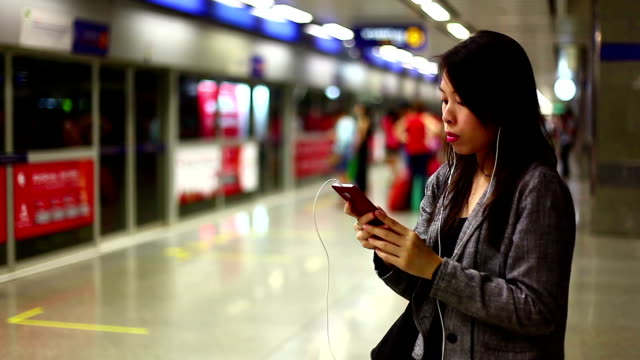 Asian woman listening music at subway station. video