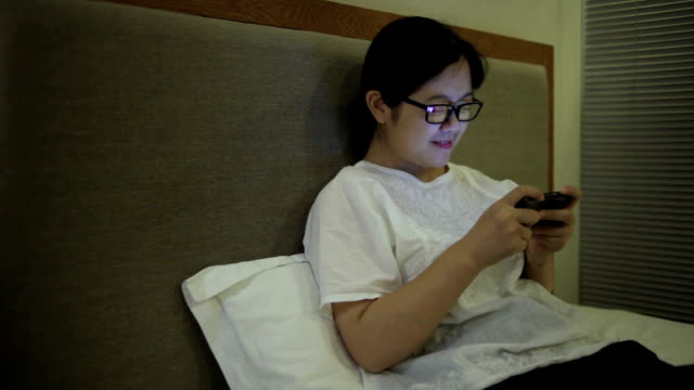 Asian woman playing mobile games indoors video
