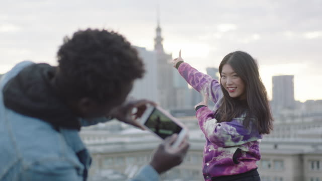 Asian woman posing on roof to photographer with smartphone video