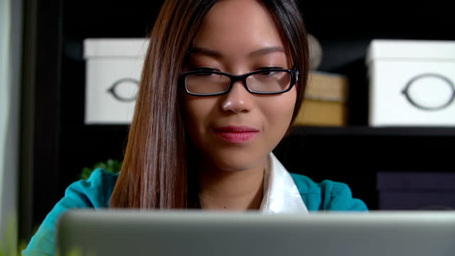 Asian woman reading a laptop computer in an office video