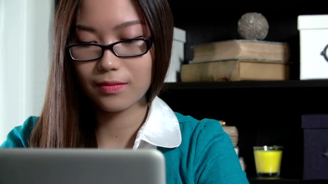 Asian woman reading a laptop computer in home office video