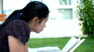 Asian woman reading book outdoor. video