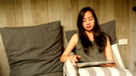 Asian woman relaxing using tablet video