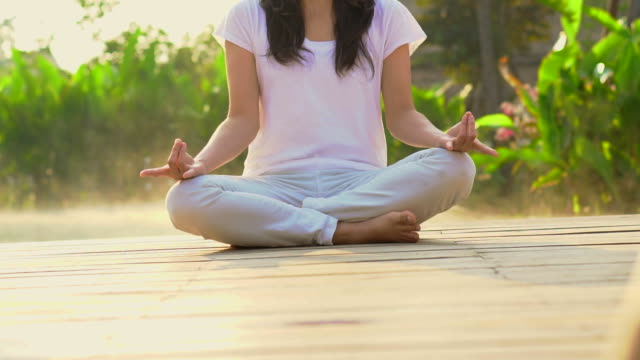Asian woman sitting and do meditation morning mist at resort and wellness pool video