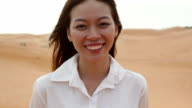 Asian woman smile outdoor desert wind blowing hair video