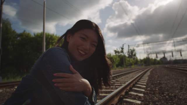 Asian woman smiling to sun on the railroad truck. video