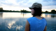 Asian woman stands near lake in sunset video