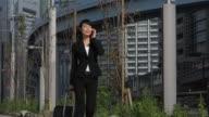Asian Woman Talking On Mobile Phone Walking Near Office Building video