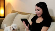 Asian Woman Talks On PC Tablet With Dog video