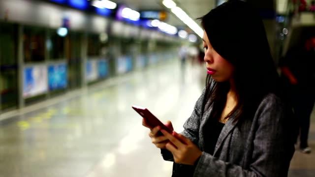 Asian woman texting at subway station. video