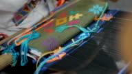 asian woman traditional hand weaving fabrics wih colorful pattern,closeup video