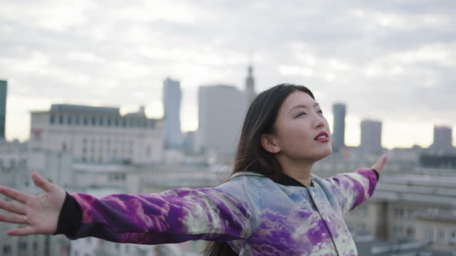 Asian woman turning on roof with opened arms video