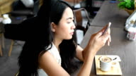Asian woman typing chat in smart phone video