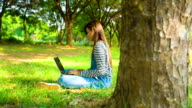 Asian woman using Laptop in the park video