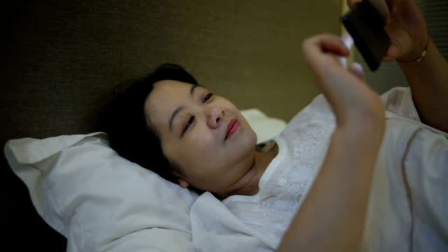 Asian woman using mobile indoors video