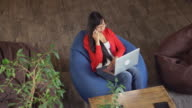 Asian woman working in loft sitting on bean bag chairs video