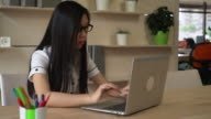 Asian woman writing text on the computer video