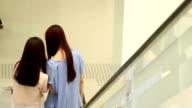 Asian women talking about phone when taking escalator in shopping mall. video
